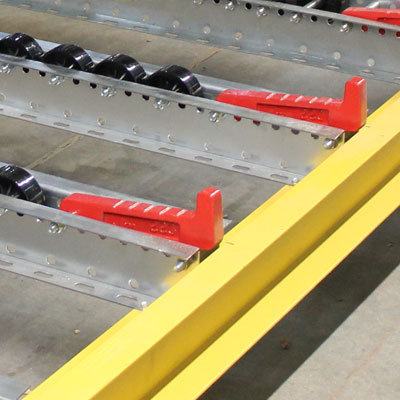 Pallet flow lanes with plastic wheels have integrated metal pallet stops to keep pallets inside the bay.